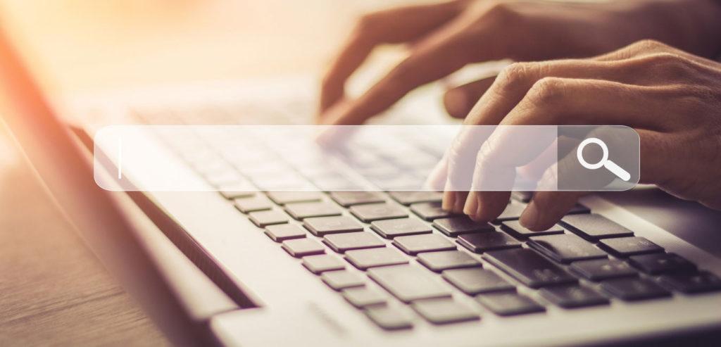 mains d'une personne effectuant une recherche en ligne